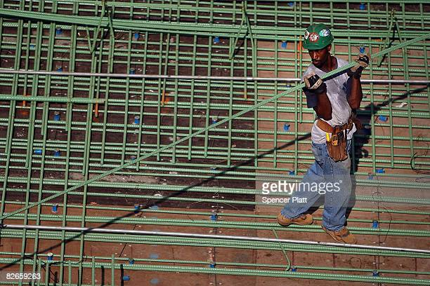 A construction worker carries a steel rod at the foundation of the Freedom Tower at the former World Trade Center site September 4 2008 in New York...