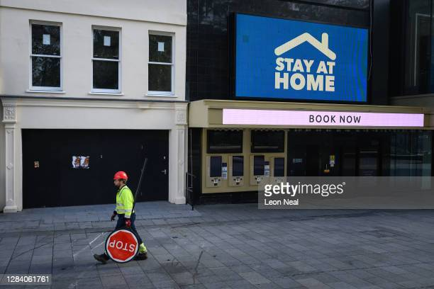 Construction worker carries a stop sign past a closed cinema in Leicester Square on November 05, 2020 in London, United Kingdom. England enters its...