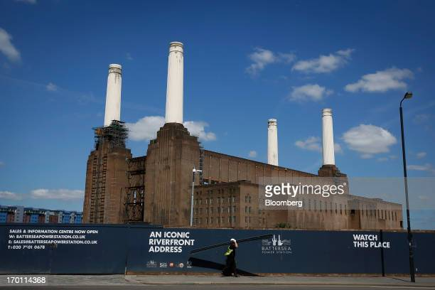 A construction worker carries lengths of wood as he walks past hoardings outside of Battersea power station in London UK on Monday June 3 2013...