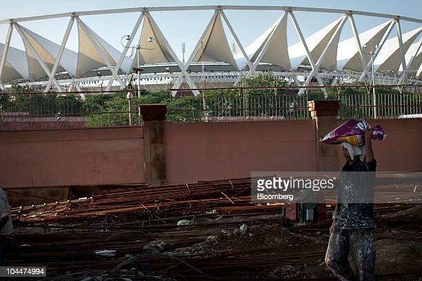 A construction worker carries objects on his head at a construction site near the Jawaharlal Nehru Stadium the primary venue for the Commonwealth...
