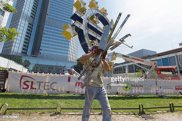 A construction worker carries scrap materials while a cherry picker operates during maintenance work on the euro sign sculpture outside the former...