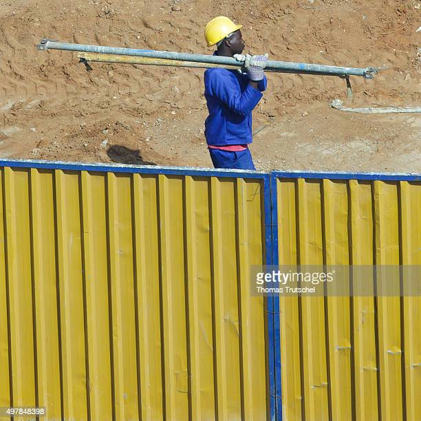 A construction worker carries steel tubes on a construction on November 19 2015 in Maputo Mozambique
