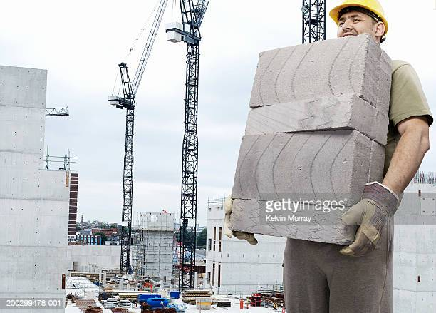 Construction worker carrying breeze blocks on building site, smiling