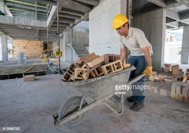construction worker carrying bricks on a wheelbarrow - wheelbarrow stock photos and pictures