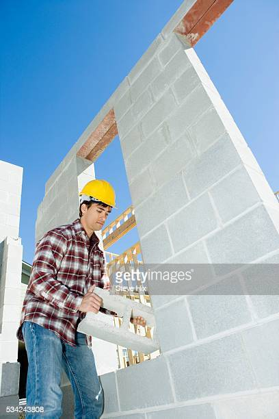 Construction Worker Carrying Cinder Block