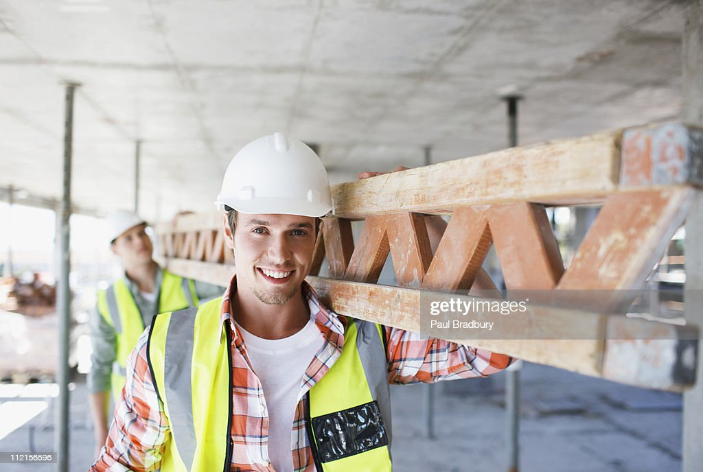 Construction worker carrying girder on construction site : Stock Photo