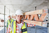 Construction worker carrying girder on construction site