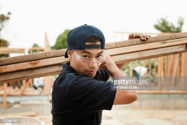 construction worker carrying lumber - community college stock pictures, royalty-free photos & images