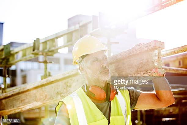 Construction worker carrying plank at site