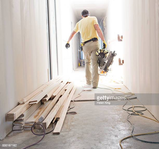 Construction worker carrying table saw