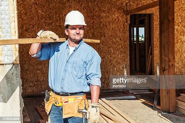 Construction Travailleur transportant des poutres en bois