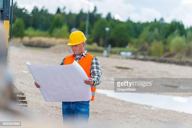 Construction worker checking blueprint