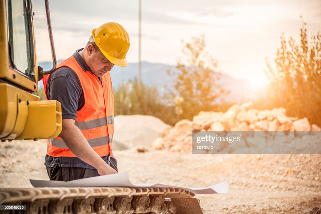Construction worker checking blueprints : Stock Photo