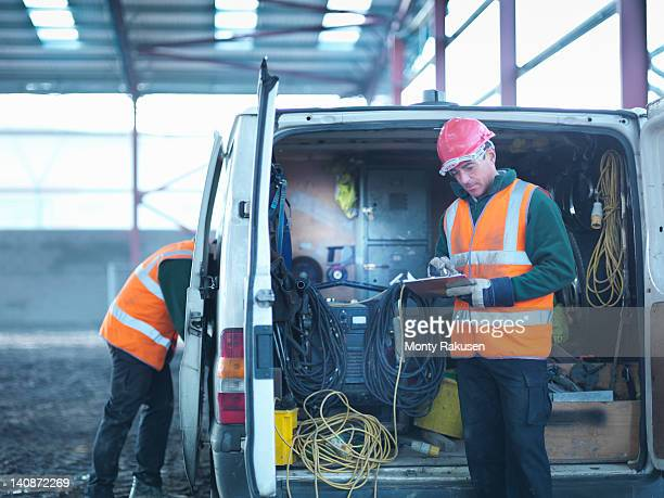 construction worker checking clipboard in back of van on building site - van stock pictures, royalty-free photos & images