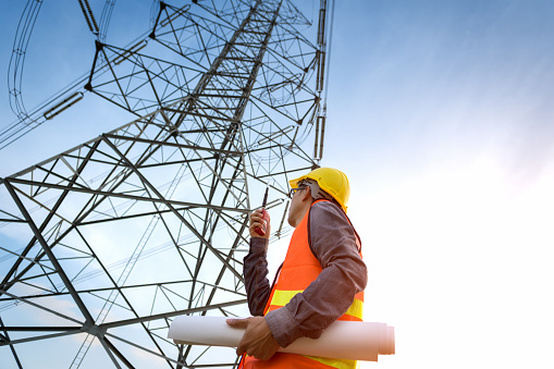 Construction worker checking location site near to High voltage tower. 1034334992