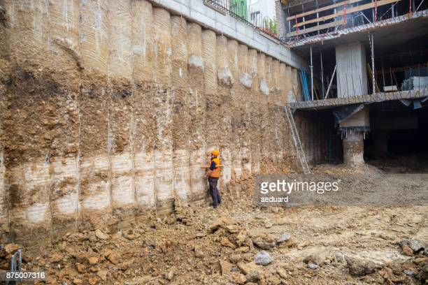 construction worker checking pile retaining wall - retaining wall stock pictures, royalty-free photos & images