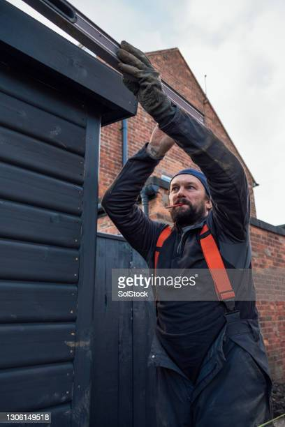 construction worker checking the level of his wall - one mature man only stock pictures, royalty-free photos & images