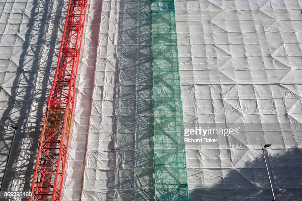 A construction worker climbs a tall gantry tower next to a crane tied to the side of an office building being renovated at the southern end of...