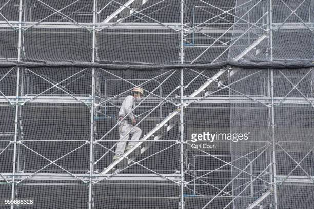 Construction worker climbs scaffolding on the New National Stadium, the main stadium for the upcoming Tokyo 2020 Olympic and Paralympic Games, on May...