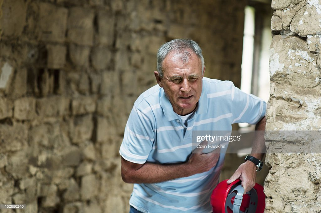 Construction worker clutching his chest : Stock Photo