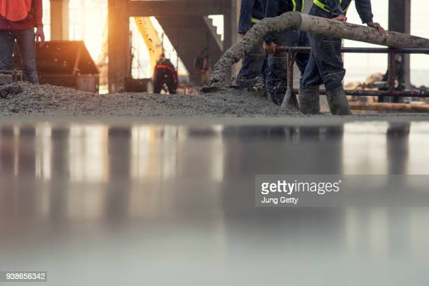 construction worker concrete pouring during commercial concreting floors of building in construction site and civil engineer - zement stock-fotos und bilder