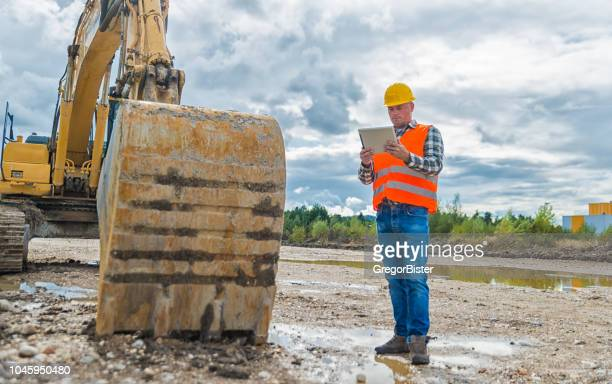 construction worker contractor using tablet computer - bulldozer stock pictures, royalty-free photos & images