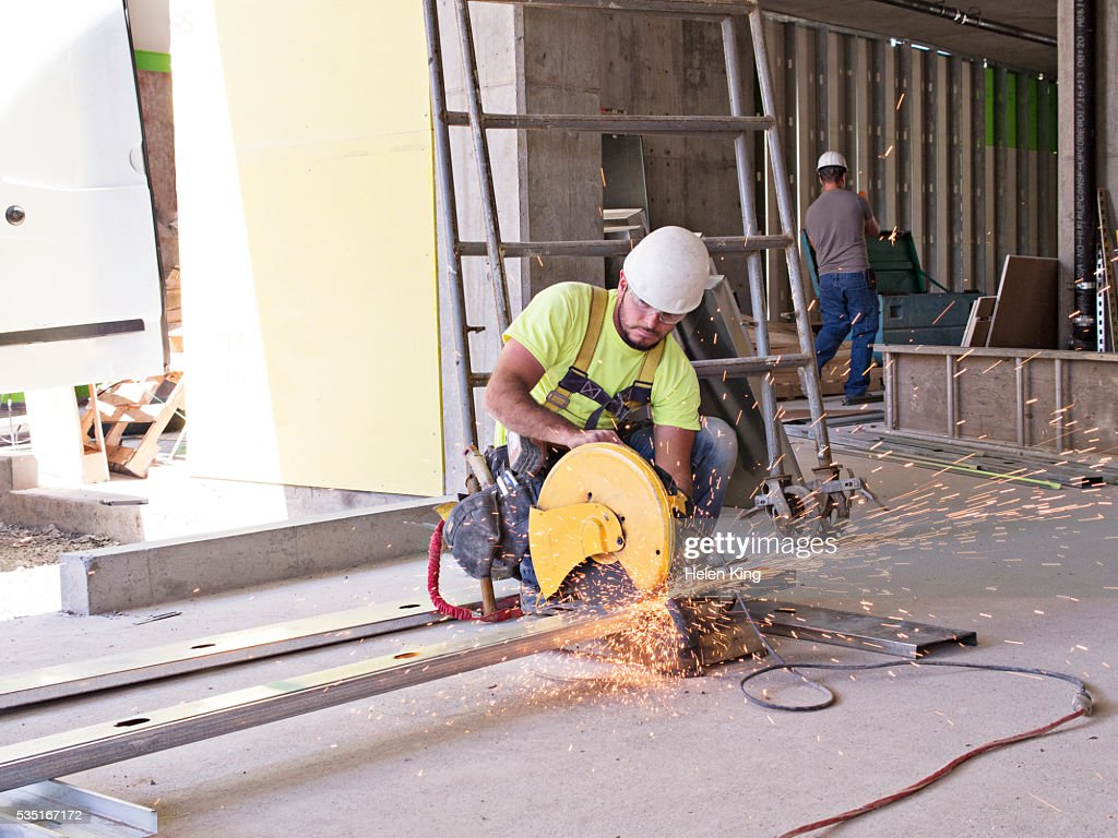 Construction worker cutting metal with circular saw : Stock Photo