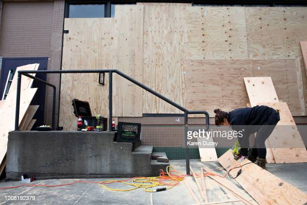 Construction worker Dani Harvey, from the property management company Blanton Turner, cuts plywood to board up the windows of an Urban Outfitters...