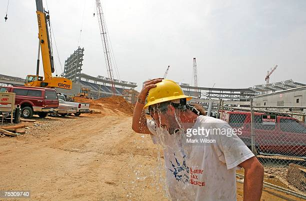 Construction worker Dennis Jenkins dumps water from his hard hat over his head while working near a new baseball stadium that is being built July 10...