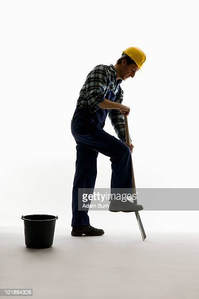 A construction worker digging with a shovel