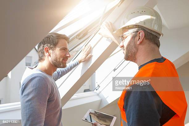 Construction worker discussing with building owner rebuilding of the apartment