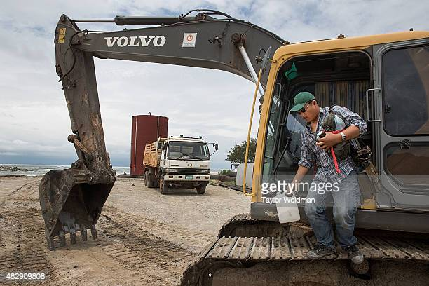 A construction worker dismounts a piece of equipment after working on the construction of a small interim port inside the planned Dawei SEZ on August...