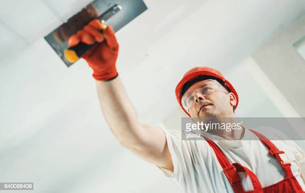 Construction worker doing finishing a ceiling.