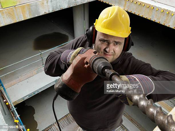 Construction worker drilling on building site