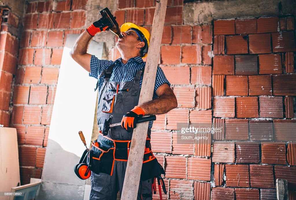 Construction worker drinking beer : Stock Photo