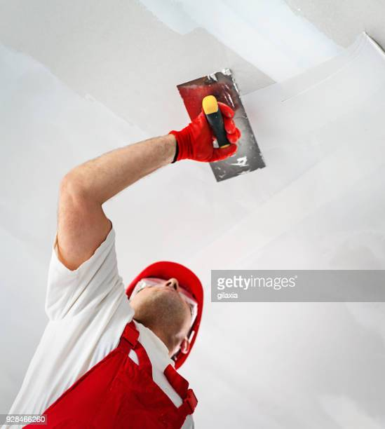 construction worker during interior decoration. - wall building feature stock pictures, royalty-free photos & images