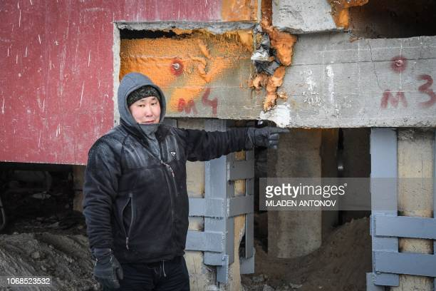 Construction worker Eduard Romanov points to a spot on a cracked panel building in the eastern Siberian city of Yakutsk on November 26 2018 Many...