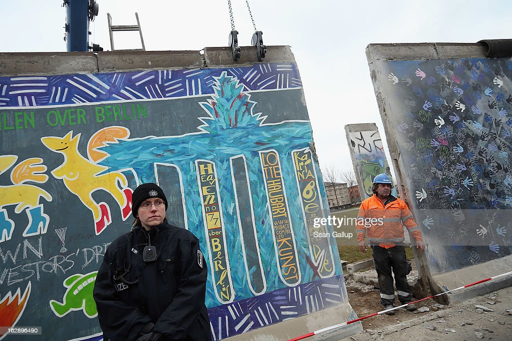 A construction worker emerges briefly from a gap while fixing equipment to a section of the East Side Gallery, which is the longest still-standing portion of the former Berlin Wall, in order to remove it with a crane as police stand nearby on March 01, 2013 in Berlin, Germany. A real estate developer is planning to build a 14-storey apartment building between the Wall and the Spree River and needs to remove a 25-meter long Wall section in order to allow access to the construction site. Critics, including East Side Gallery mural artists and Spree River embankment development opponents, decry the move, citing the importance of the East Side Gallery's status as a protected landmark and a major tourist attraction. The East Side Gallery is approximately 1.3 kilometers long.