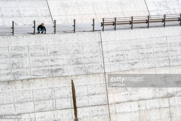 A construction worker erects a barrier on a concrete seawall in Toni Bay near Kamaishi one of the towns hit by the 2011 Tohoku earthquake and tsunami...