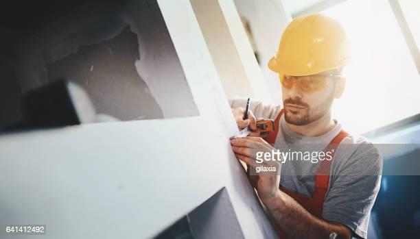 bouwvakker onderzoeken een gipsplaat. - aanbrengen stockfoto's en -beelden