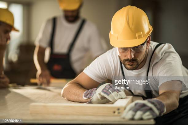 construction worker examining plank while working on home renovation process. - foundation make up stock pictures, royalty-free photos & images