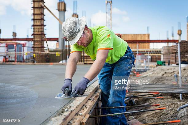 Construction worker finishing concrete at construction site
