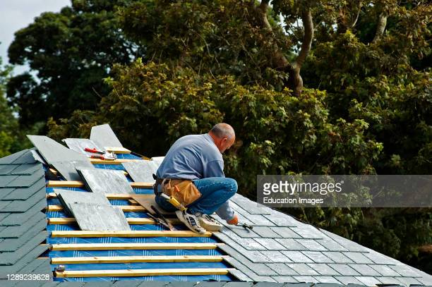 Construction worker fixing the roof of a residential property, England, uk.