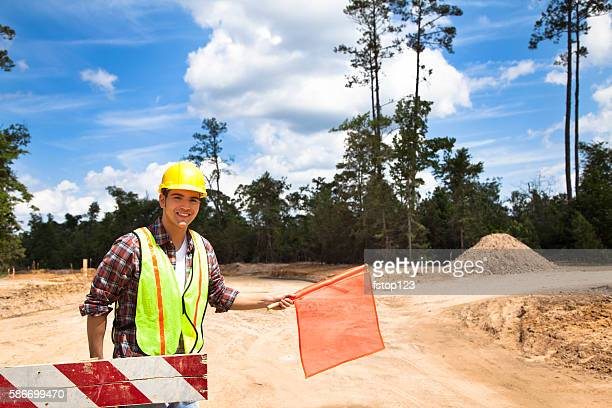 Construction worker, flagman directs traffic at job site.