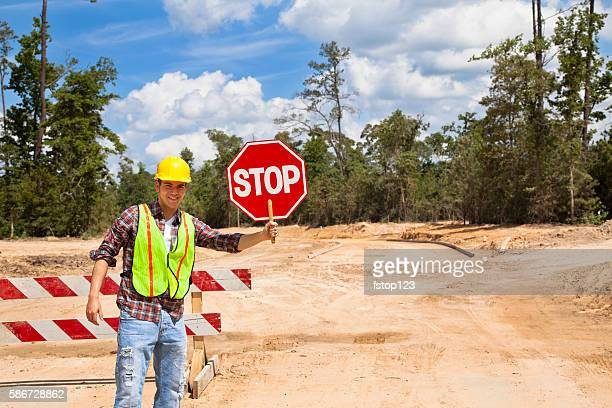 Construction worker, flagman holds stop sign at job site.