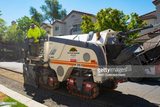 A construction worker for American Asphalt wearing a bright yellow high visibility vest steers a machine as it removes asphalt during a road...