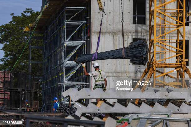 Construction worker guides steel reinforcement rods in a winch at a residential apartment construction site, on a plot of brownfield land in the...