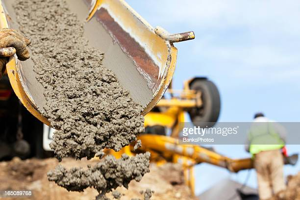 construction worker guiding cement mixer truck trough - concrete stock pictures, royalty-free photos & images