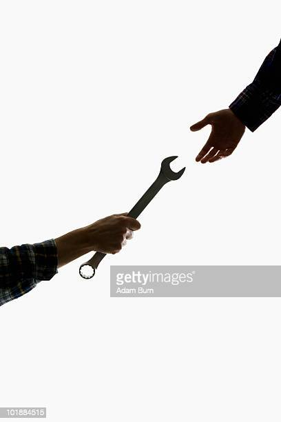 A construction worker handing a wrench to another worker, focus on hands