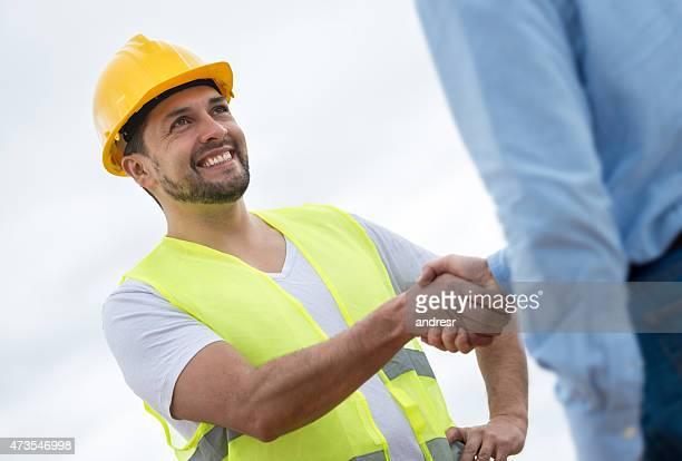 Bau Arbeiter handshaking mit einem Architekten